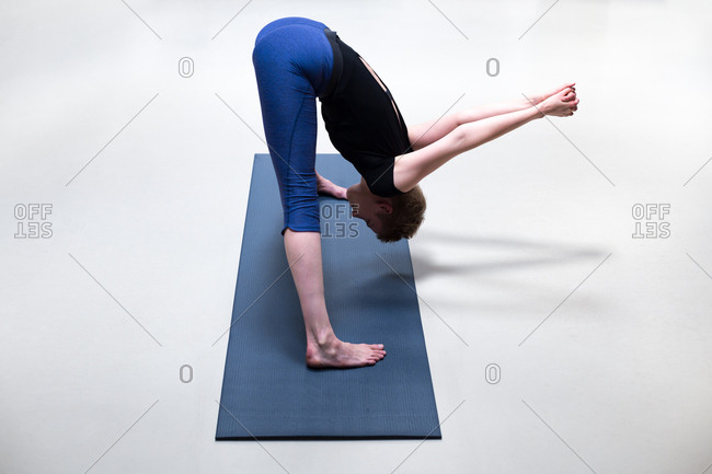 Young woman doing yoga on a blue mat with a white background