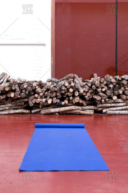 Blue yoga mat in the foreground of a studio with logs in the background
