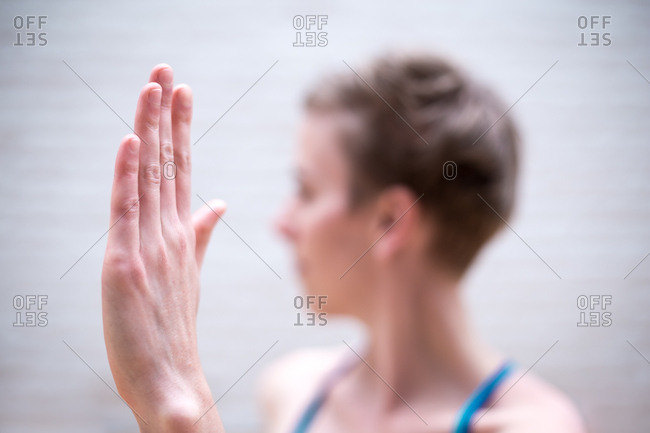 Young woman doing yoga with her hand in sharp focus