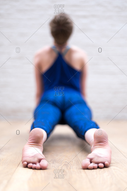 Young woman doing yoga with her feet in focus