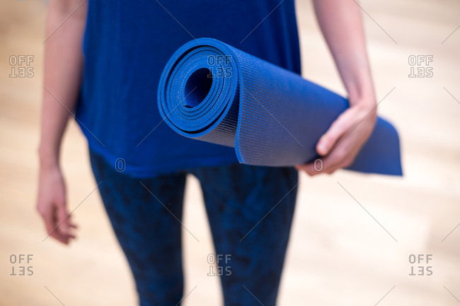 Young woman dressed in blue yoga clothes with a blue yoga mat
