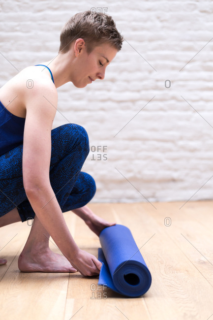 Young woman unrolling a blue yoga mat in a studio