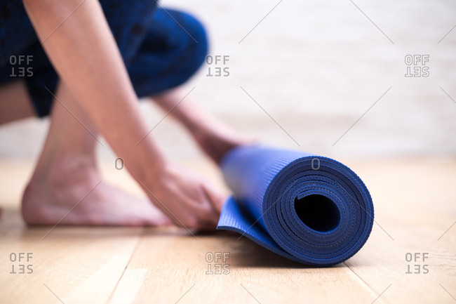 Young woman unrolling a blue yoga mat
