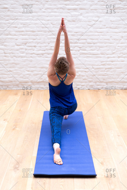 Young woman dressed in blue performing yoga on a blue mat