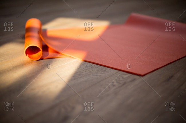 Orange yoga mat bathed in sunlight on a wood floor