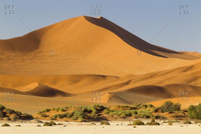 Africa, Namibia, Namib Desert, Namib-Naukluft National Park, Sossusvlei. Large red dune rising from a while pan.