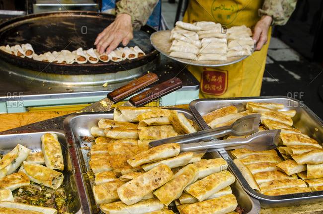 Muslim Hui woman preparing food, Muslim market, Xian, China.