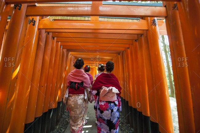 Japan, Honshu, Kansai Region, Kyoto, Fushimi-Inari Taisha shrine, women dressed like Geisha walking through the Orange-Red Torii gates