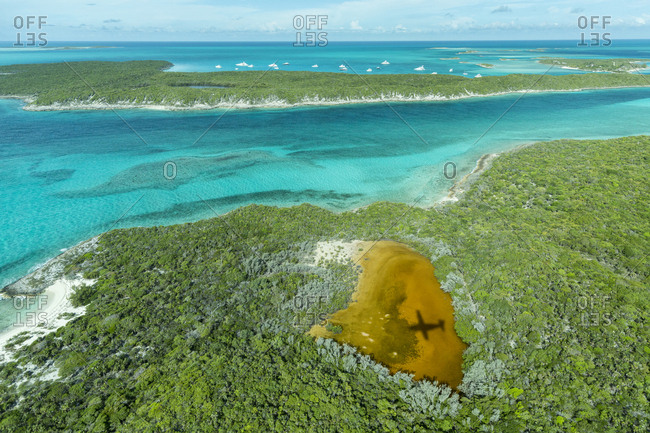 Aerial photo looking down at the airplane's shadow and clear tropical water and islands in the Exuma Chain of islands the Bahamas near Staniel Cay.