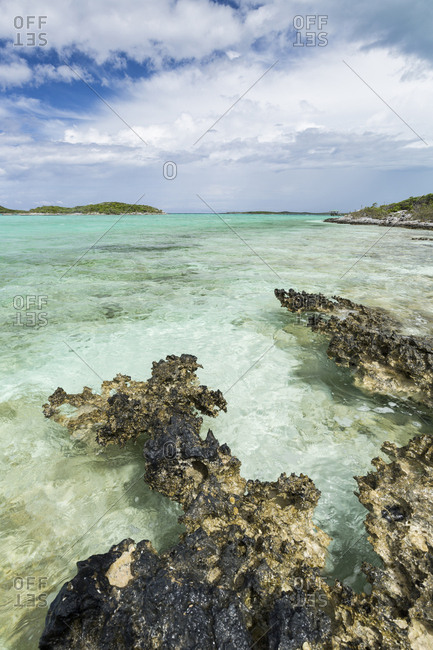 Limestone rocks in the foreground with clear water and blue skies in the background as seen on Staniel Cay, Bahamas.