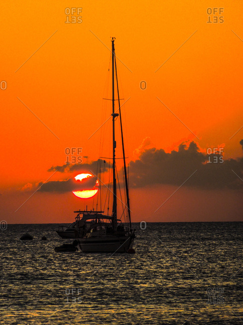 Seven Mile Beach, Grand Cayman. Sailboat and a boat with the orange sun setting behind the clouds on the Caribbean Sea