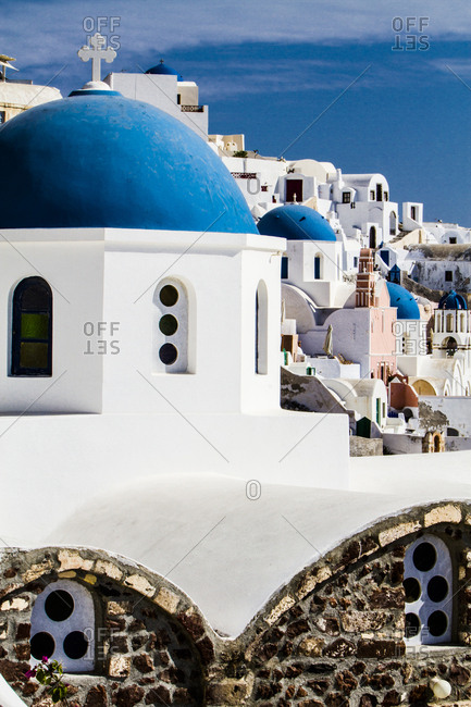 Oia, Greece. Row of Greek Orthodox Churches with blue domes and painted pastel white washed buildings