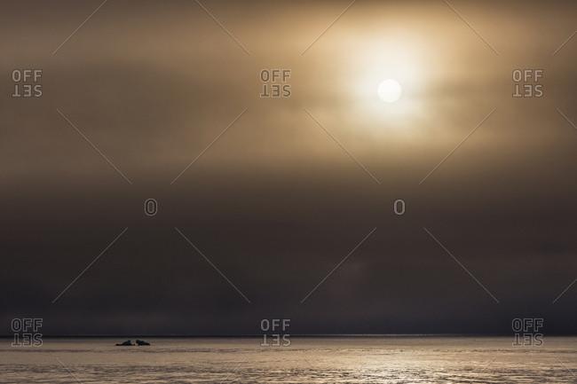 Norway, Svalbard, Kvitoya. Iceberg and fog bank at sunrise.