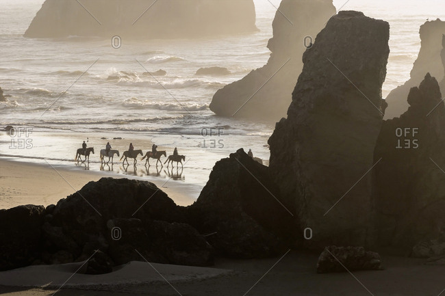 USA, Oregon, Bandon. Horseback riders on beach.