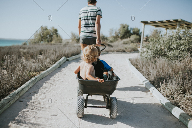 Man pulling toddlers to beach in wagon