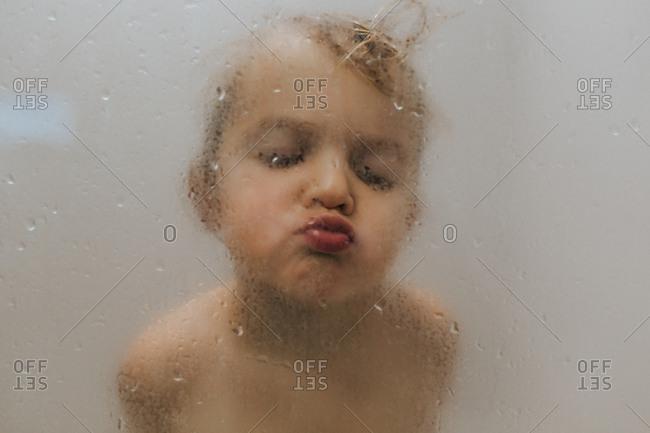 Cute toddler boy making a face through fogged up glass