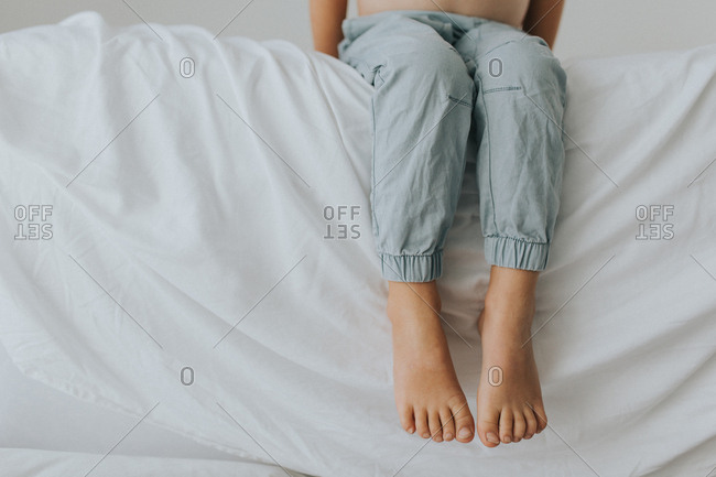 Young child's feet and toes dangling over edge of bed