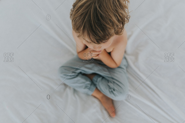 Overhead view of young boy sitting on bed