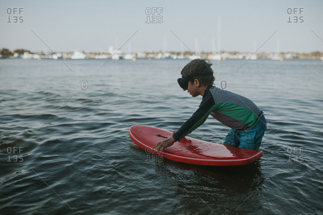 Boy in swim mask playing with boogie board in water