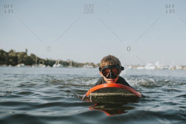 Boy kicking on boogie board in water