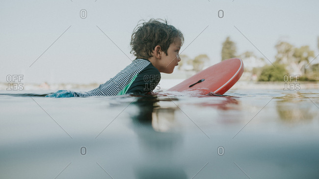 Young boy swimming on boogie board in water