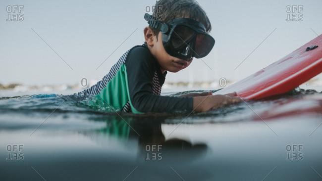 Boy in swim mask floating on boogie board