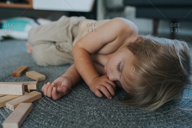 Boy sleeping on floor next to wooden blocks