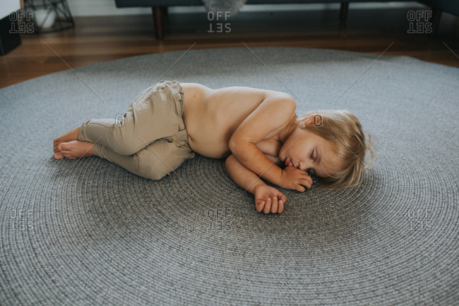 Toddler child asleep on floor while sucking his thumb