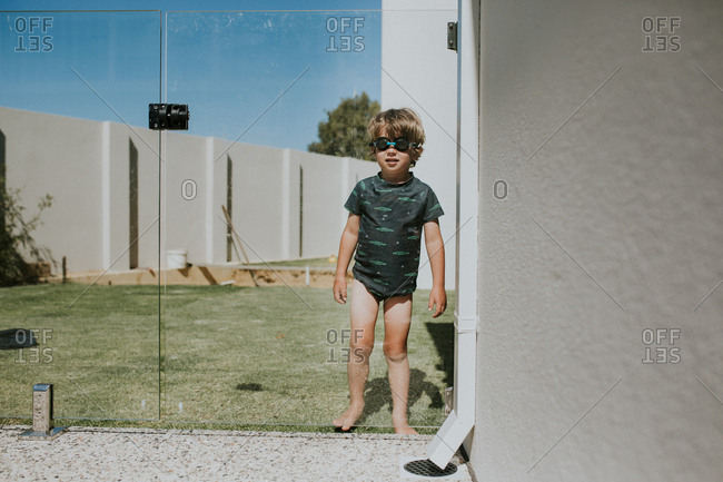 Boy in swim goggles behind glass fence