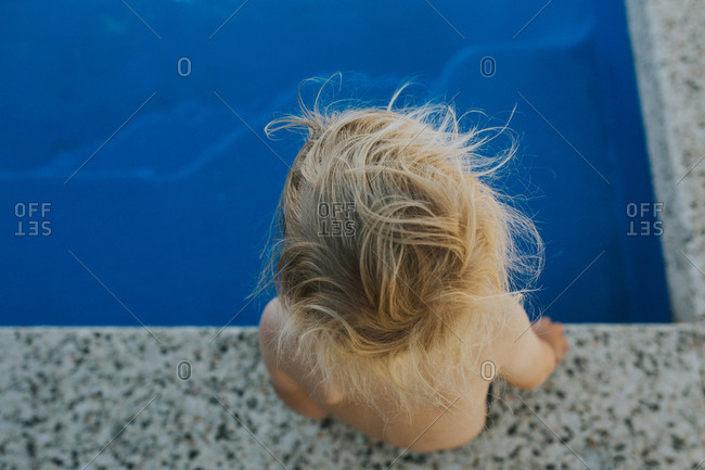 Overhead view of blond child seated at edge of pool