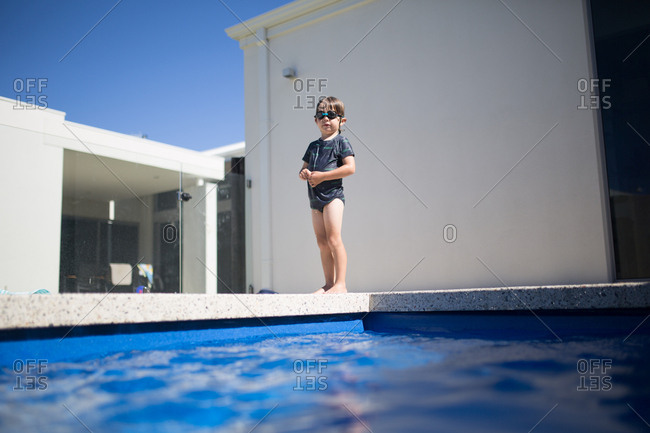 Young child in swim goggles standing at edge of pool