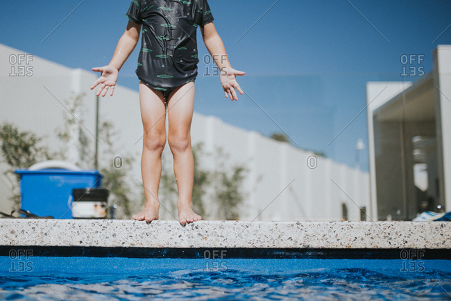 Child standing at edge of swimming pool