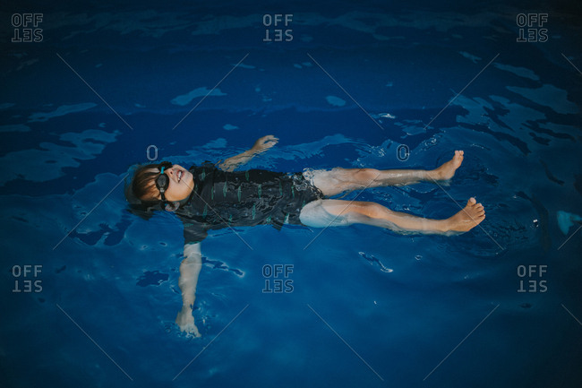 Child floating on back in swimming pool