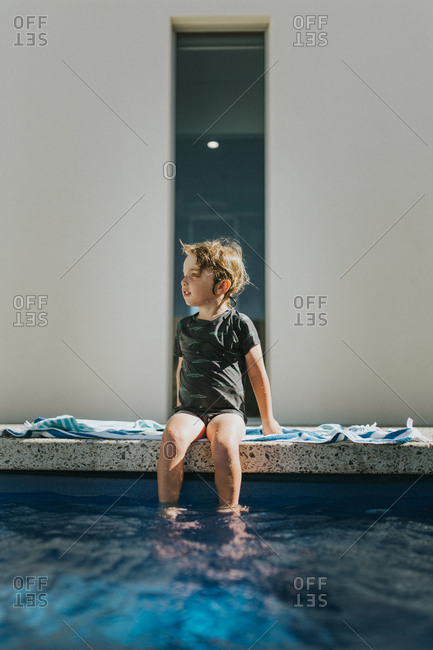 Child sitting on towel at edge of swimming pool