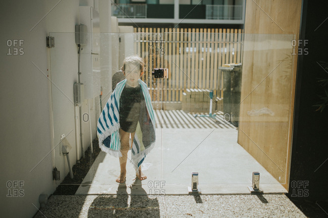 Child wrapped in towel standing at glass fence