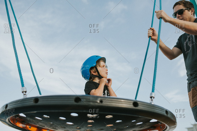Father and son playing on playground swing