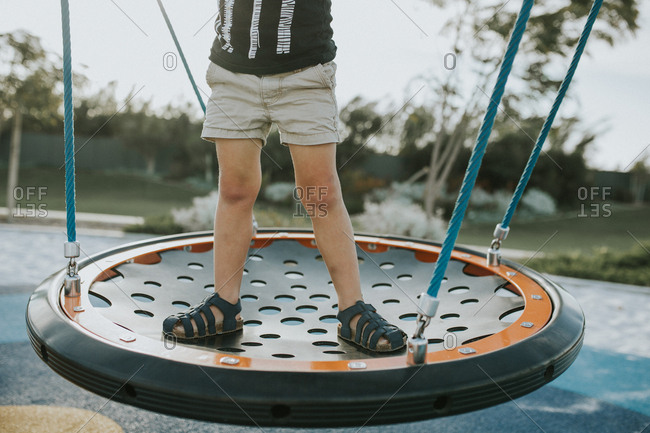 Child standing on round swing