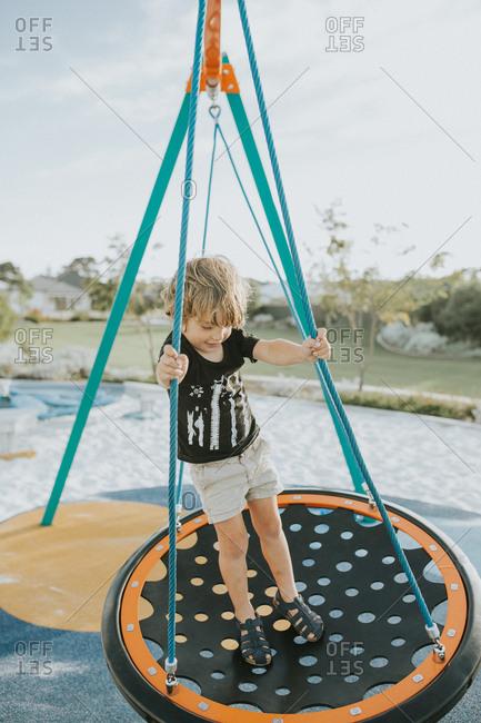 Preschooler standing on round swing at playground