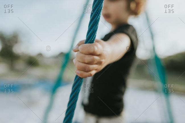 Child holding onto rope at playground