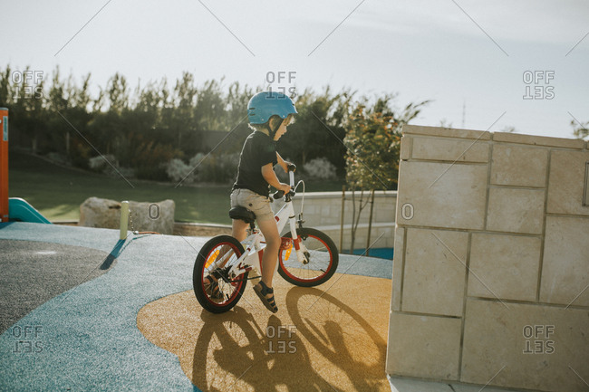 Young boy riding bicycle on playground