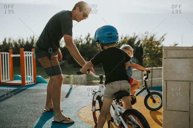 Man helping sons on bicycles at playground