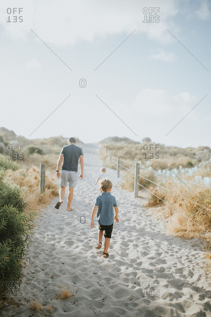 Father and two children walk on sandy path to beach
