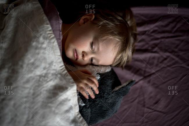 Sleepy girl cuddling with stuffed animal in bed