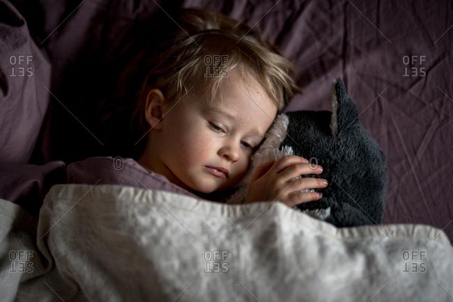 Sleepy child cuddling with stuffed animal in bed