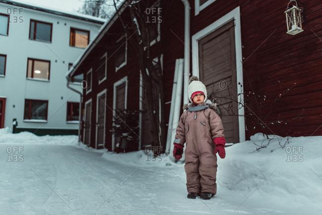 Little girl walking on wintery street in Finland