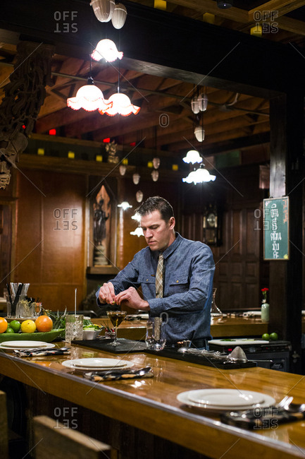 Lyle, Washington - January 4, 2017: Man preparing a cocktail behind bar