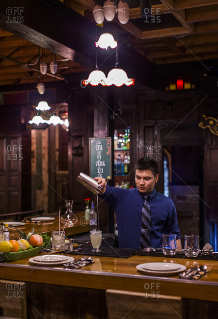Lyle, Washington - January 4, 2017: Bartender pouring cocktail from shaker
