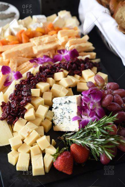 Cheese plate decorated with flowers and rosemary