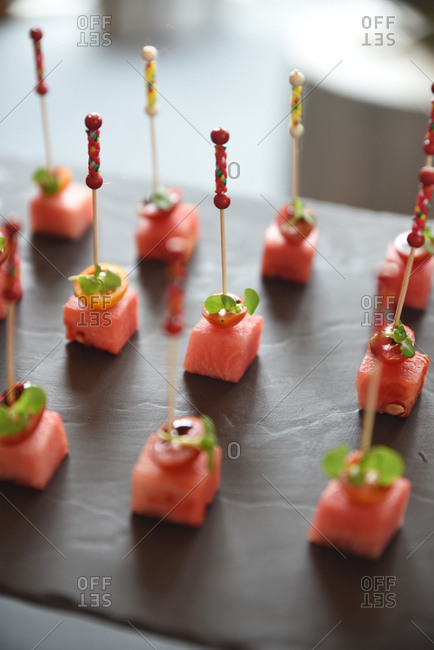 Cubes of watermelon on toothpicks with tomatoes and herbs
