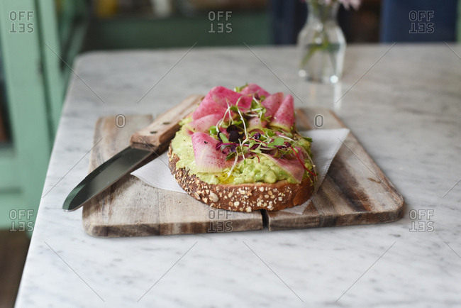 Piece of bread topped with thinly sliced fruit and avocado